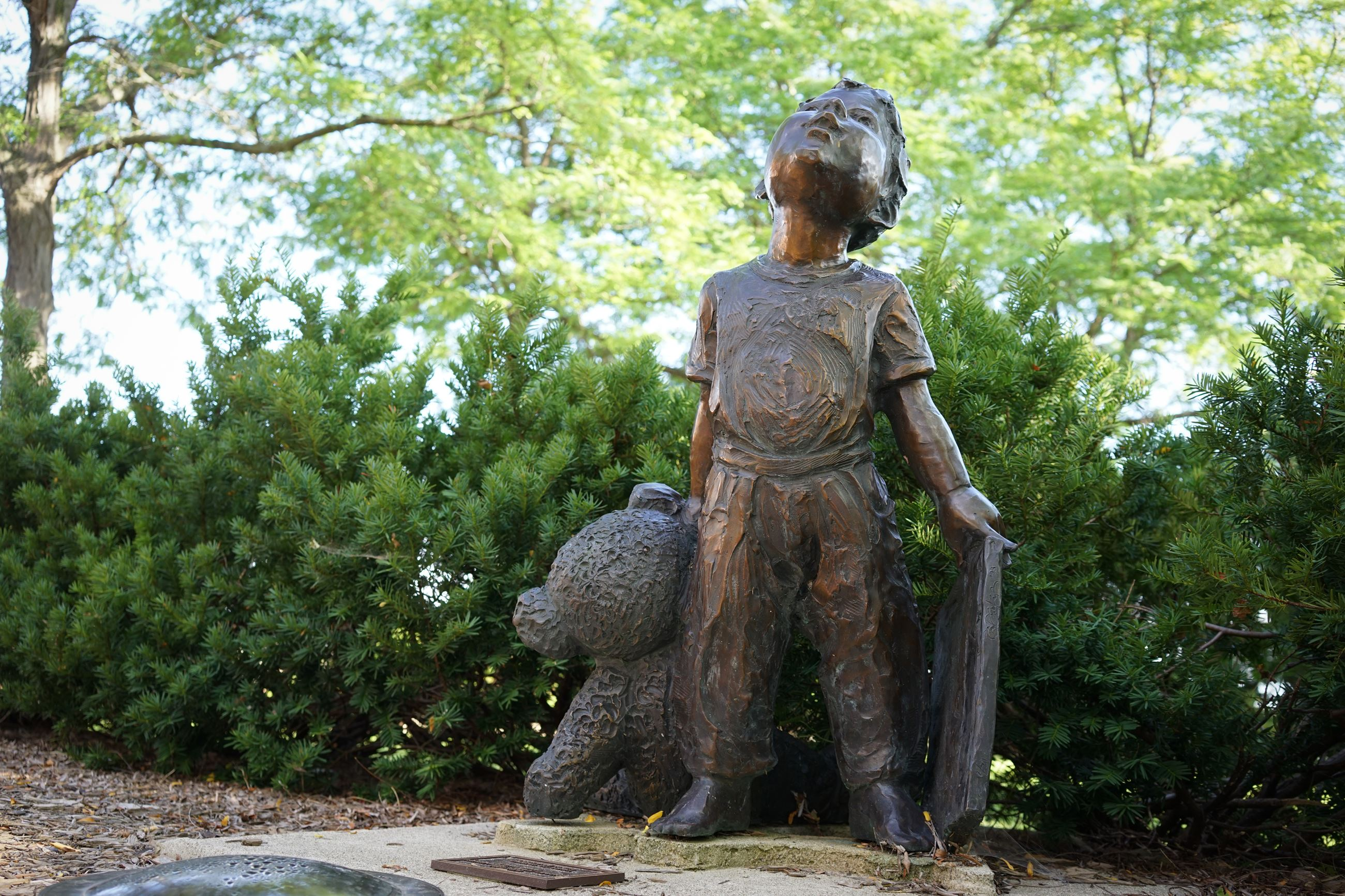Image of bronze statue of a small boy and a bear cub.