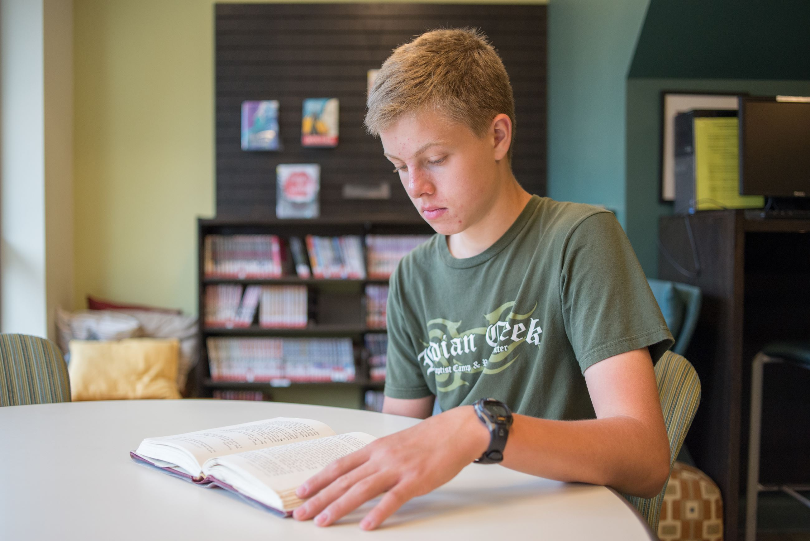 Image of teenage boy reading a book at a table