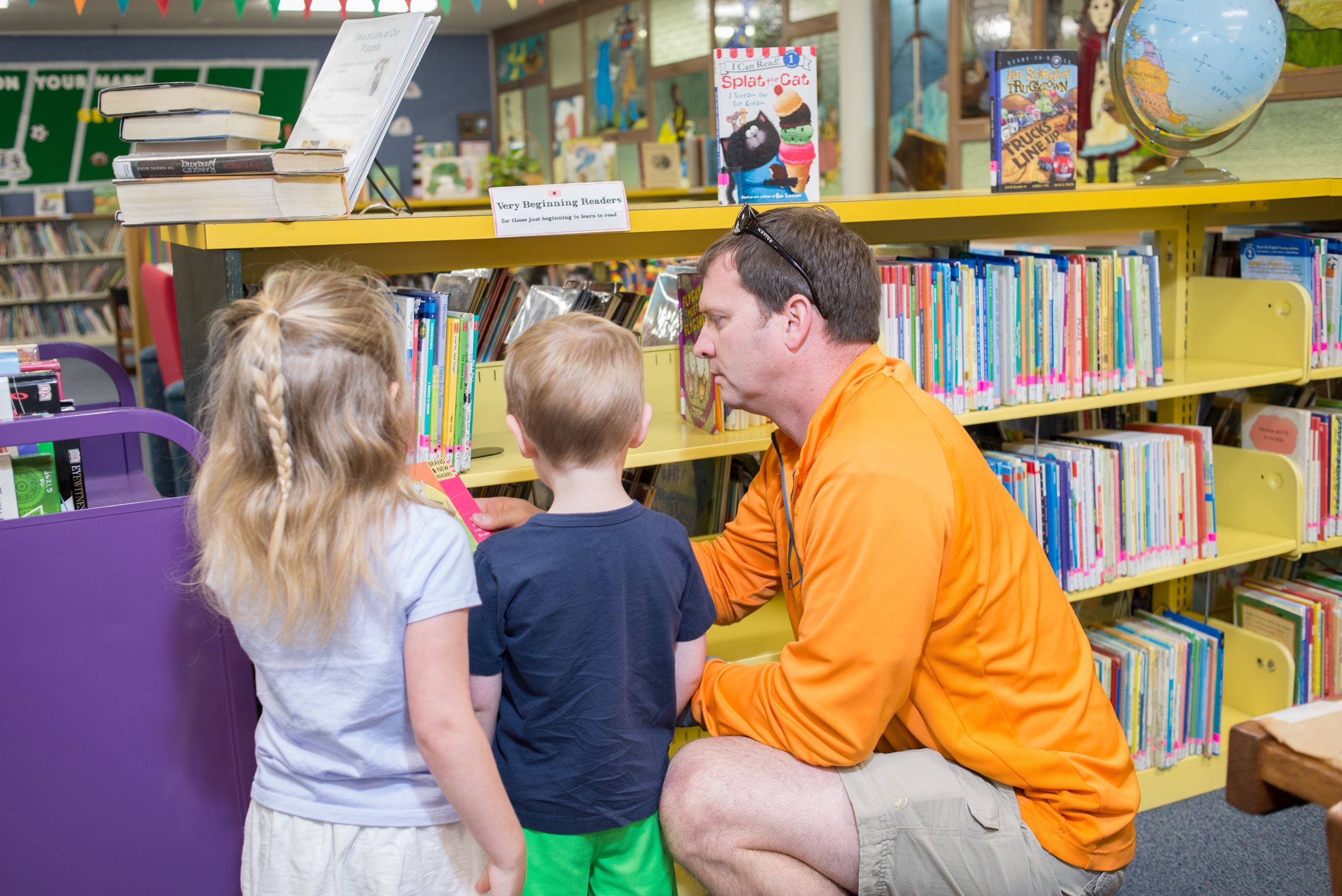 Image of father and children in front of book shelves