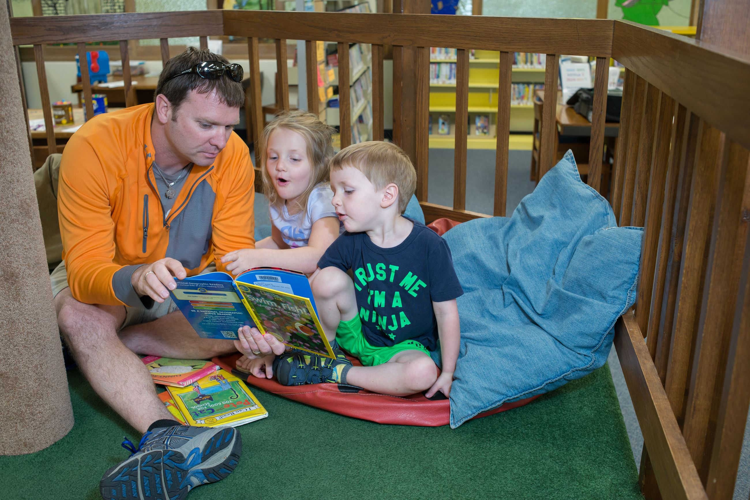 Image of father reading to children in a pretend tree house